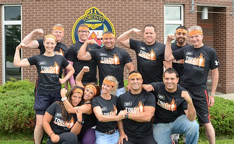 A group of men and women flexing one arm wearing black T-shirts in front of a TPS logo on a brick wall