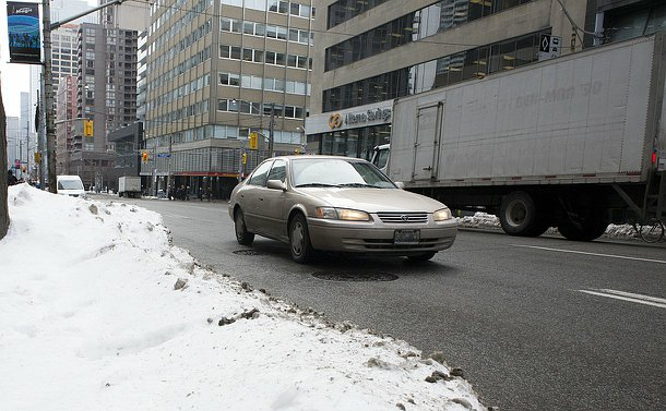 A car driving past a snowbank in downtown area with large buildings surrounding