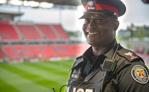 A man in TPS uniform with stadium field in background