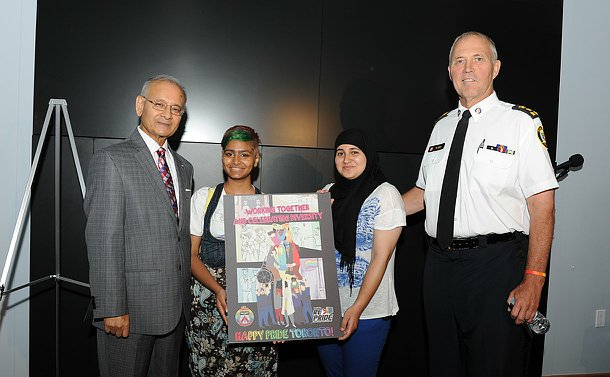 Two teenage girls holding a poster flanked by two men, one in TPS uniform