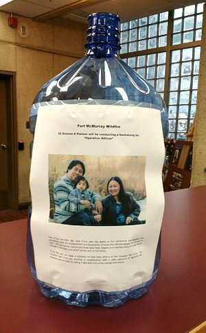 A water cooler jar overturned with a photo of a family accompanied by text too small to be read