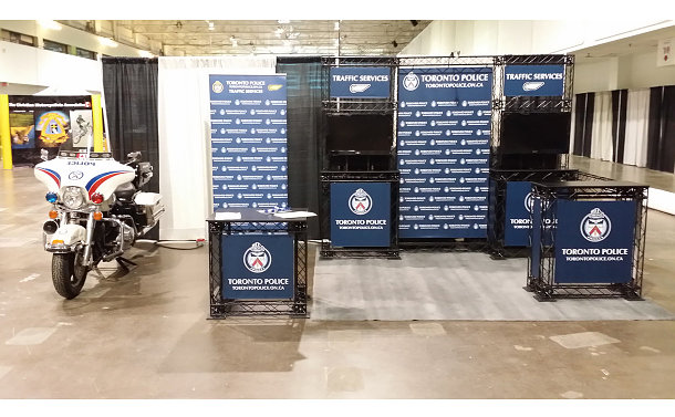 A display booth with TPS crests and a motorcycle