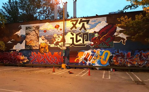 A mural on a large brick wall in front of a parking lot