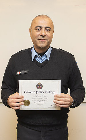 A man in TPS parking uniform holding a certificate