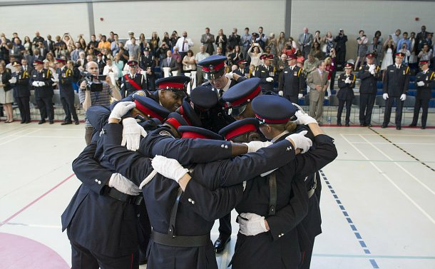 A group of TPS officers huddle in front of an audience