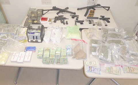 Several table with guns and plastic bags of drugs