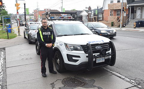 A man in uniform standing next to a police vehicle in a busy intersection