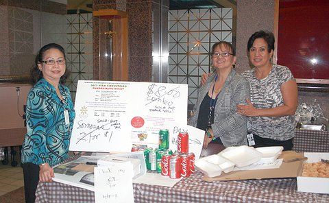 Three women stand with a table of food with signs