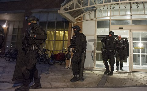 Men in police tactical gear leave a building entrance