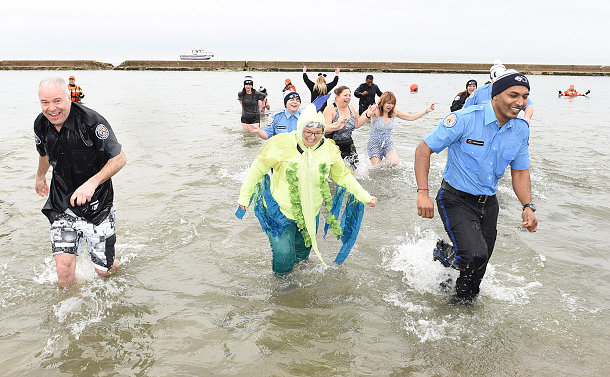 People running clothed in water