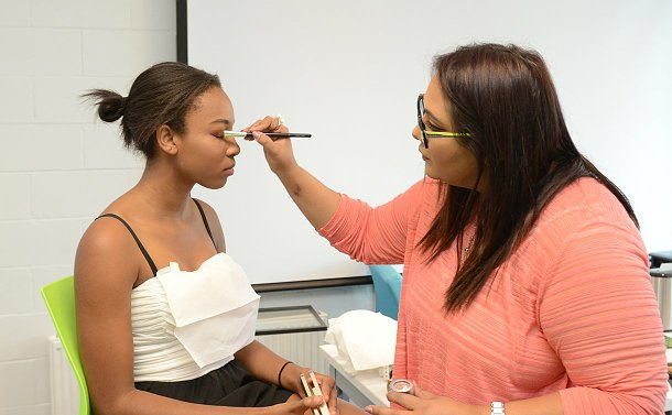 A woman applies makeup on a teenage girl