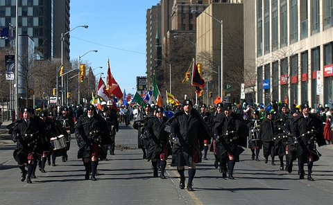 A group of men and women in TPS uniform on a street with flags in background