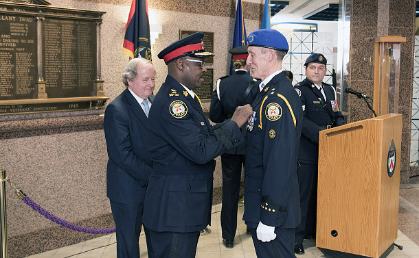 Two men in police uniforms, one pinning a medal to the other's chest, while another man in a suit looks on