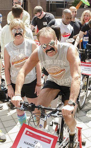 A man wearing a fake moustache pedalling a stationary bicycle and a woman with a fake moustache looking on