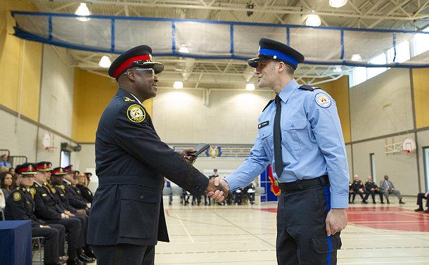 A man in TPS police uniform hands a wallet to a man in TPS special constable uniform