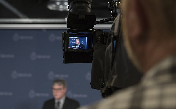 A man at a podium and viewed in eyepiece of video camera