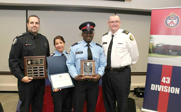 Three men and one women in TPS uniform holding plaques