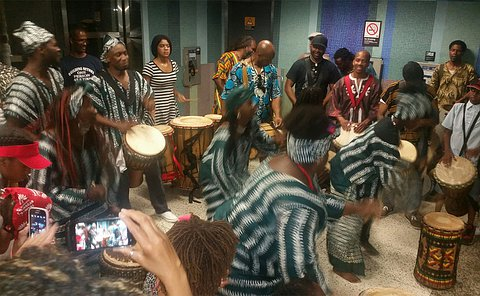 A group of people in a circle hand drumming as others take photos
