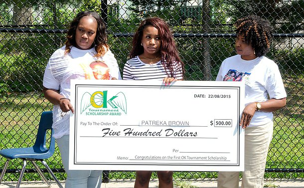 Two women and a girl holding up a large cheque for five hundred dollars