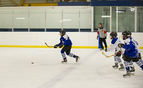 A child in hockey uniform skating away from a group of three others on a hockey rink