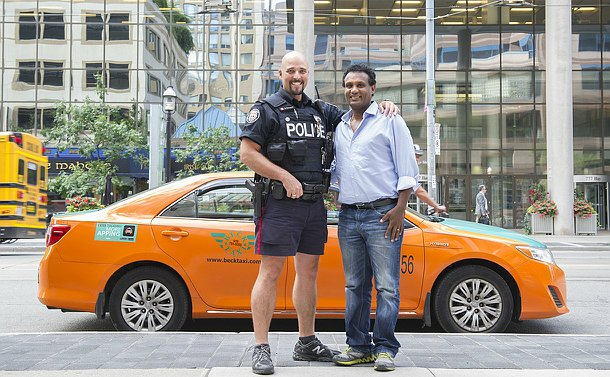 A man in TPS uniform stands beside another man in front of a taxi