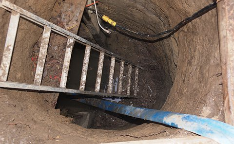 A ladder leading underground with electrical cables running into it