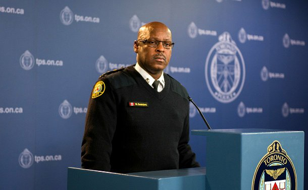 A man in TPS uniform stands at a podium