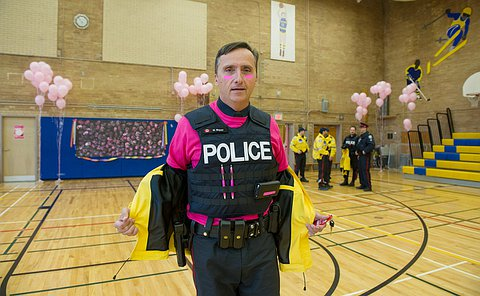 An officer in uniform, wearing a pink shirt underneath his vest and pink stripes on his face.