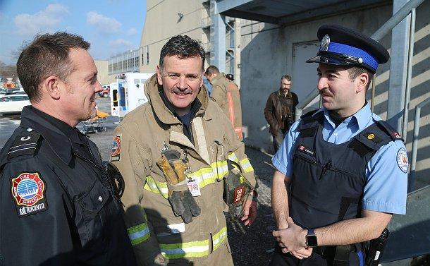 Two men in Toronto Fire uniform speak with a  man in TPS Court uniform
