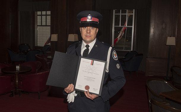 A man in TPS uniform holding a certificate