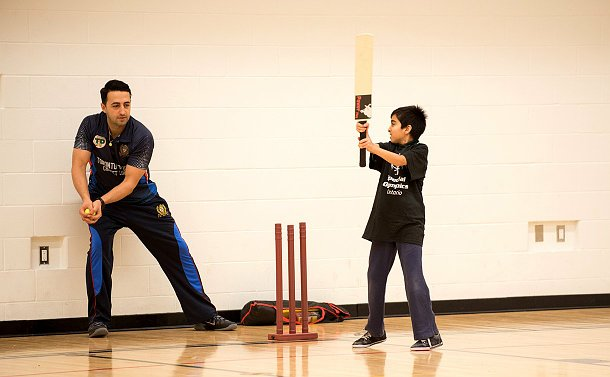 A boy in a sports jersey standing to bat at a crease with a police officer standing behind the wicket