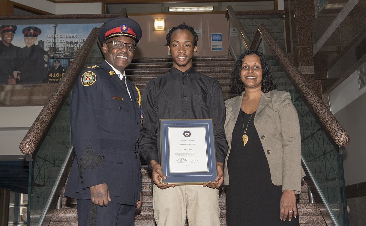 A man in TPS uniform with a man holding a framed certificate and a woman