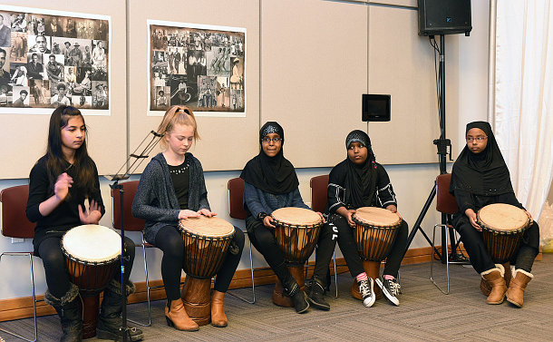 Group of five female junior students sitting and playing drums