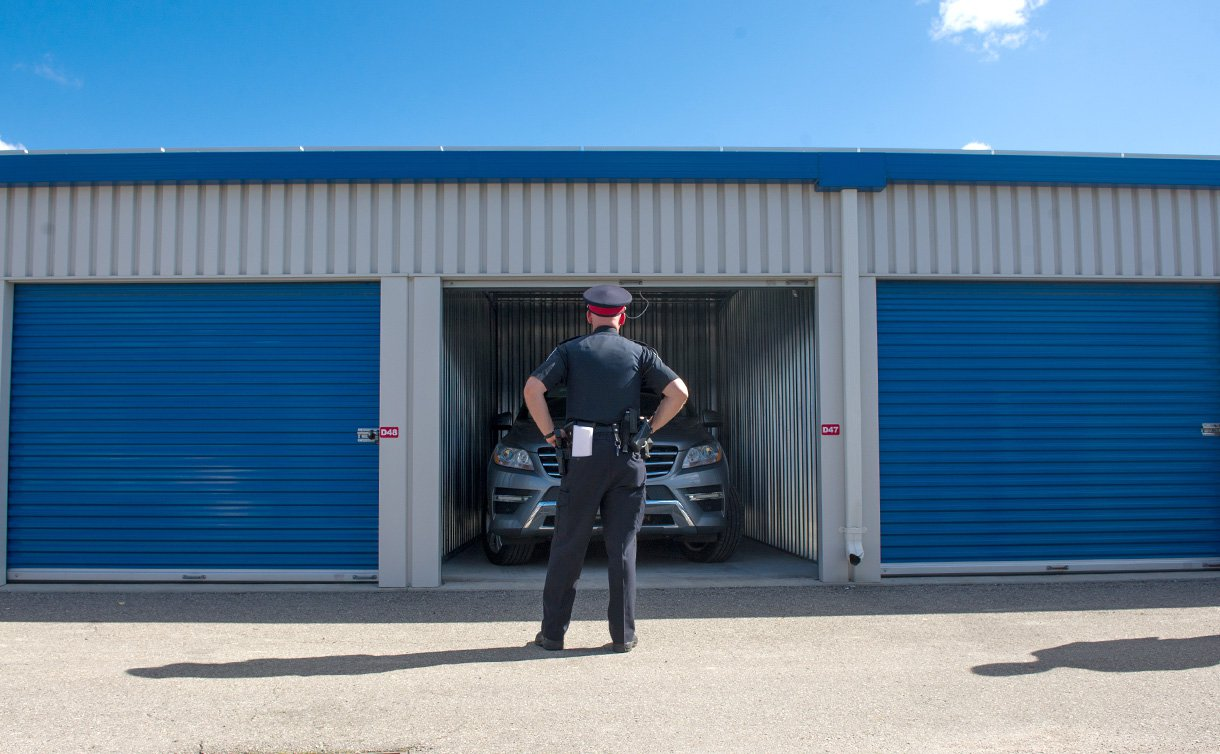 A man in TPS uniform stands in front a row of closed garage doors with one open door containing a vehicle