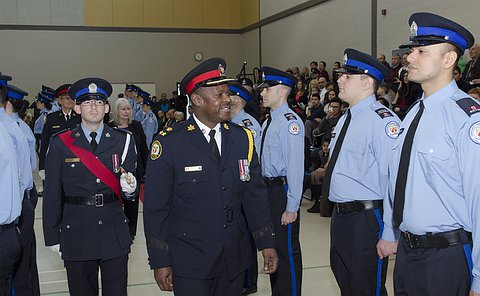 A man in TPS uniform smiling walks down a row of men and women in TPS court officer uniform