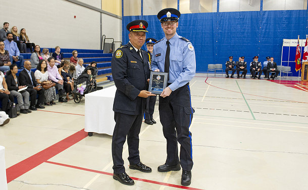 A man in TPS uniform holding a plaque with a man in Parking uniform