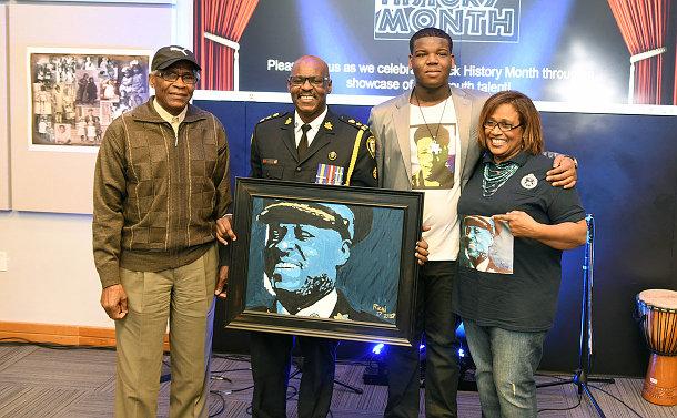 Man in a police uniform in the middle is holding a painting of himself, while two men, one older and one younger flank him, with a woman standing to the right