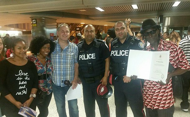 Two men in TPS uniform pose for a photo with others