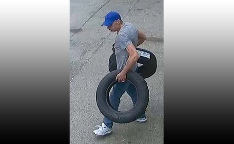 A man walking holding two tires
