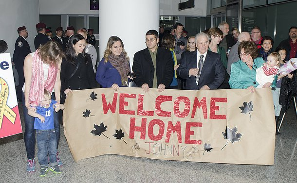 A group of people young and old behind a banner reading welcome home Johnny