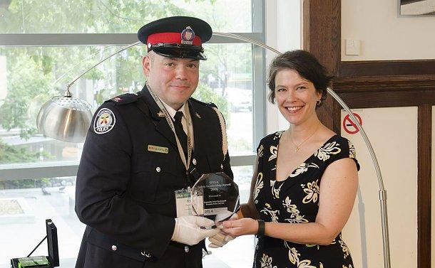 A man in TPS uniform holds an award beside a woman