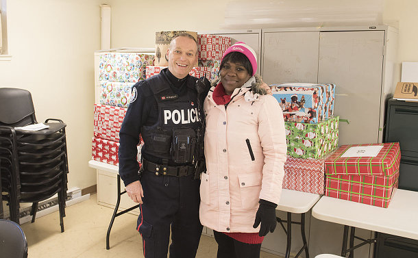 A man in TPS uniform with a woman and wrapped gifts