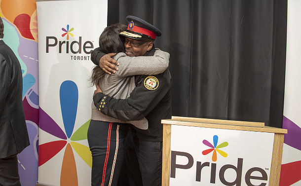 A man in TPS uniform hugs a woman
