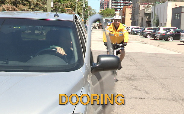 A person opens their car door in the path of a cyclist