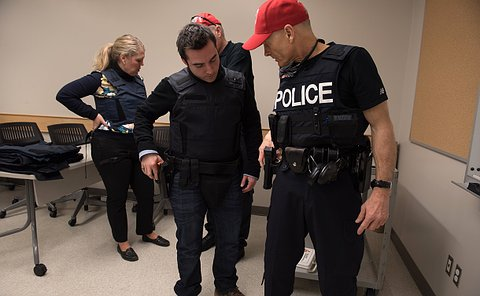 Aman wearing a bulletproof vest looks at an officer in uniform as he holds a gun in a holster