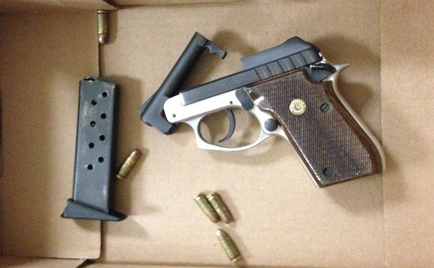 A black and silver handgun with bullets around it in a cardboard box