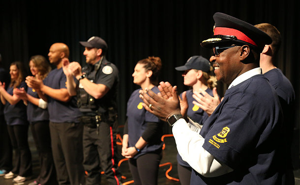 A group of people clapping, some in TPS uniform
