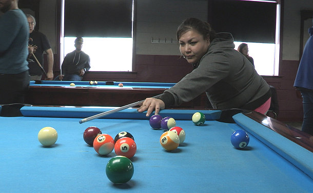 A woman plays billiards