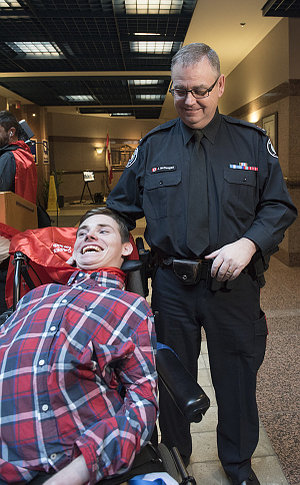 A man in TPS uniform with another man in a wheelchair