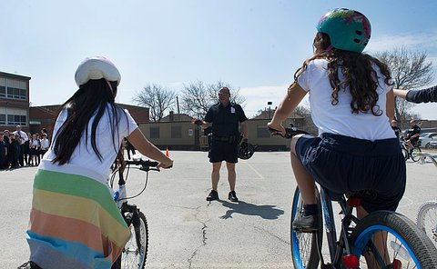 an officer standing in front of children who are on cycles.